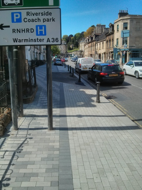 Pedestrian path blocked by road sign so pedestrians forced into cycle track.