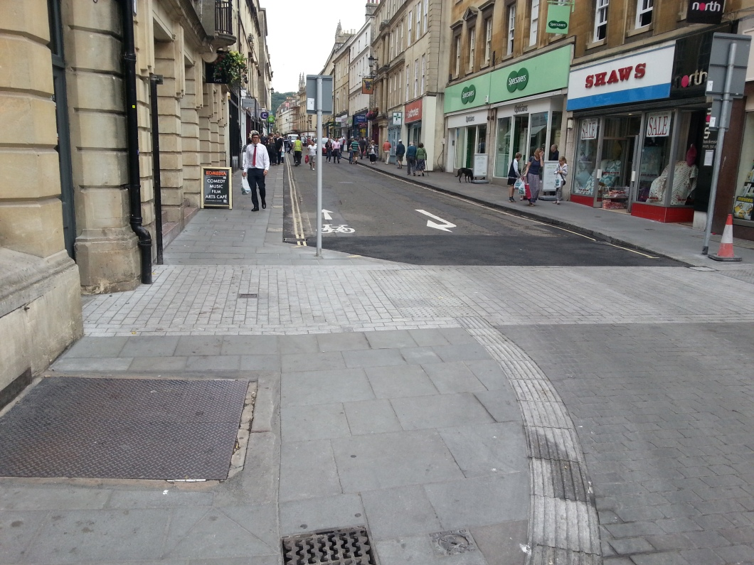 View from Flan OBrien's towards Westgate Street. Existing contraflow in place. Note tyre marks showing how tightly cars are taking the corner directly into the path of cyclists coming down the contraflow from Saw Close. Cars need a wider line of attack.